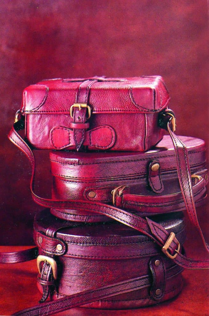stack of varied red leather bags with straps and buckles